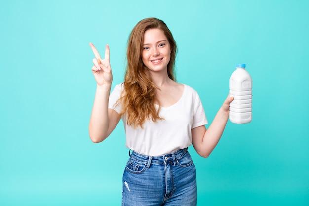 Lächelnd und freundlich aussehend, nummer zwei zeigend und eine milchflasche haltend