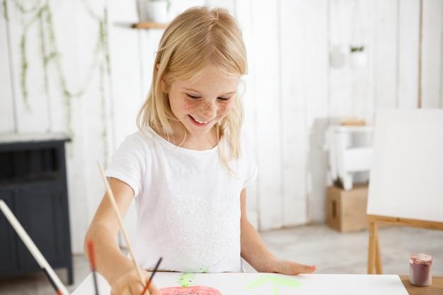 Lächelnd und fröhlich, voller freude kind mit blonden haaren und sommersprossen, die pinsel in der hand halten und strebend bild im kunstraum malen.