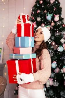 Lächelnd und glücklich hält junge frau in winterkleidung viele verpackte geschenkboxen vor sich in der nähe des weihnachtsbaumes. mädchen genießen weihnachtsgeschenke, grüßen neujahr und weihnachten, feiertagskonzept.