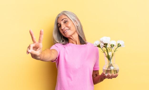 Lächelnd und glücklich, sorglos und positiv aussehend, sieg oder frieden mit einer hand mit dekorativen blumen gestikulieren