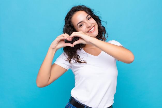 Lächelnd und glücklich, süß, romantisch und verliebt, mit beiden händen herzform machen