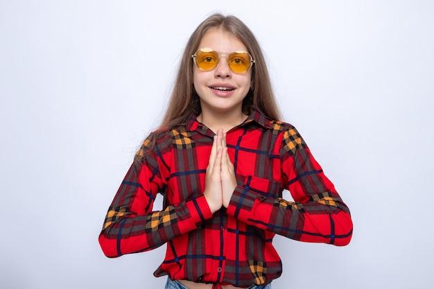 Lächelnd zeigend beten geste schönes kleines mädchen mit rotem hemd und brille