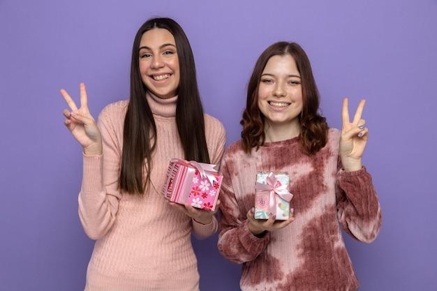 Lächelnd zeigende friedensgeste zwei mädchen, die geschenke halten