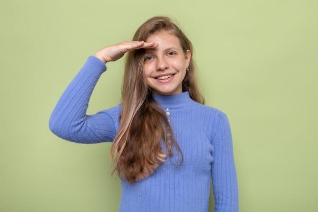 Lächelnd zeigende grußgeste schönes kleines mädchen mit blauem pullover isoliert auf olivgrüner wand