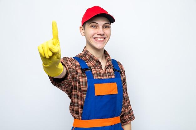 Lächelnd zeigt einen jungen putzmann in uniform und mütze mit handschuhen