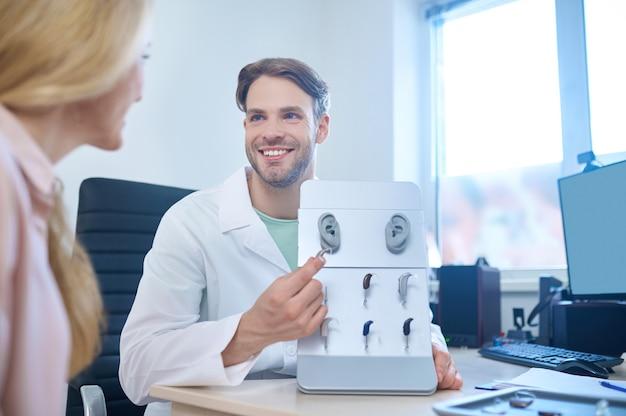 Lächelnd zufriedener, gutaussehender männlicher audiologe, der einer blonden frau eine vielzahl von hörgeräten zeigt