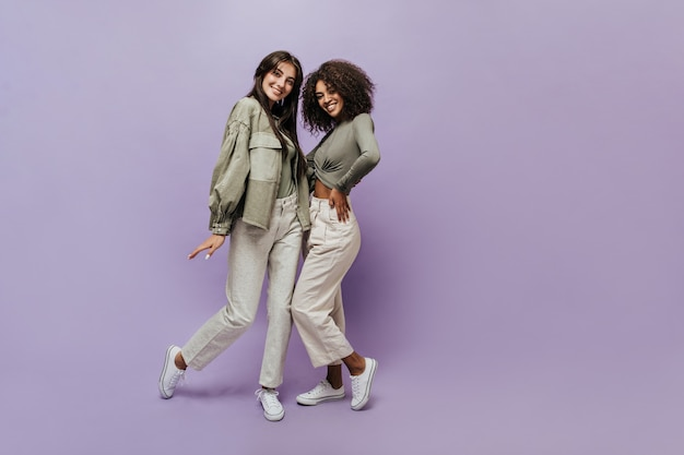 Lächelnd zwei coole frauen mit brünetten frisur in olivfarbenen hemden, beige weiten hosen und weißen trendigen turnschuhen, die in die kamera schauen
