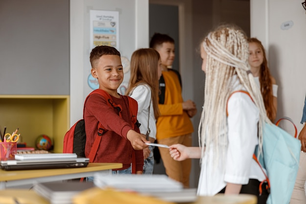 Lächelnd zwei klassenkameraden mit rucksäcken, die in der klasse stehen