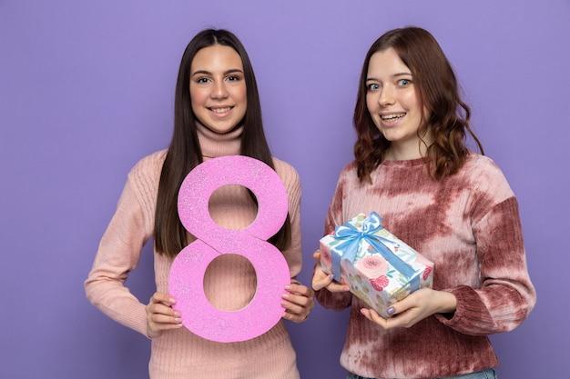 Lächelnd zwei mädchen am glücklichen frauentag mit der nummer acht mit geschenk
