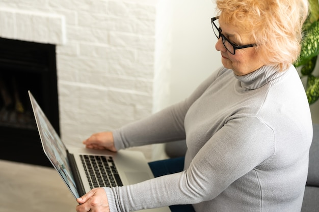 Lächelnde ältere ältere frau mit laptop zu hause.