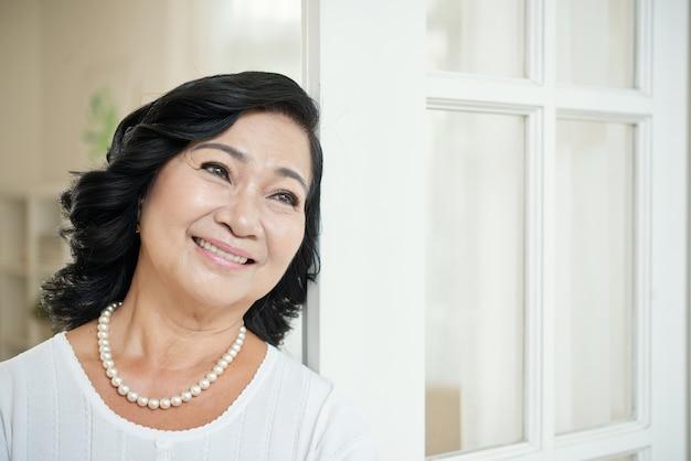 Lächelnde ältere asiatin, die sich zu hause auf tür lehnt und weg schaut