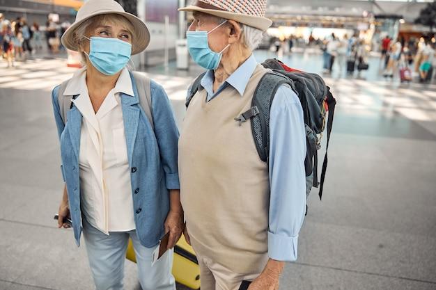 Lächelnde ältere dame mit einer bordkarte und einem ausländischen pass, die ihren mann anlächelt