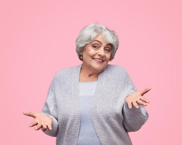 Lächelnde ältere dame zuckte mit den schultern