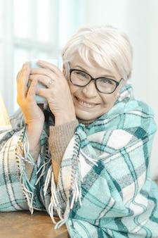 Lächelnde ältere frau, die an etwas denkt und eine tasse tee hält.