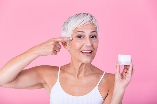 Lächelnde ältere frau, die antialternlotion anwendet, um dunkle kreise unter augen zu entfernen. reife frau, die kosmetische creme verwendet, um falten zu verstecken. dame, die tagesfeuchtigkeitscreme verwendet, um der hautalterung entgegenzuwirken.