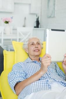 Lächelnde ältere frau, die auf dem gelben sofa betrachtet digitale tablette sich entspannt
