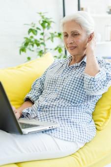 Lächelnde ältere frau, die auf dem sofa betrachtet laptop sitzt