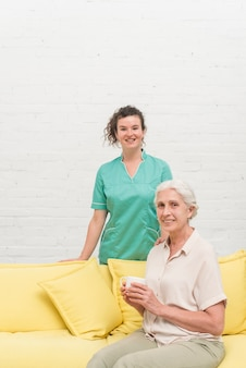 Lächelnde ältere frau, die auf dem sofa hält kaffeetasse vor krankenschwester sitzt