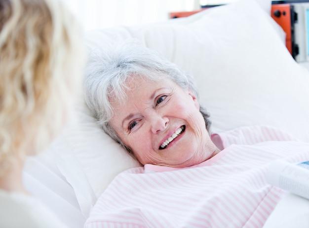 Lächelnde ältere frau, die auf einem krankenhausbett spricht mit ihrer enkelin liegt