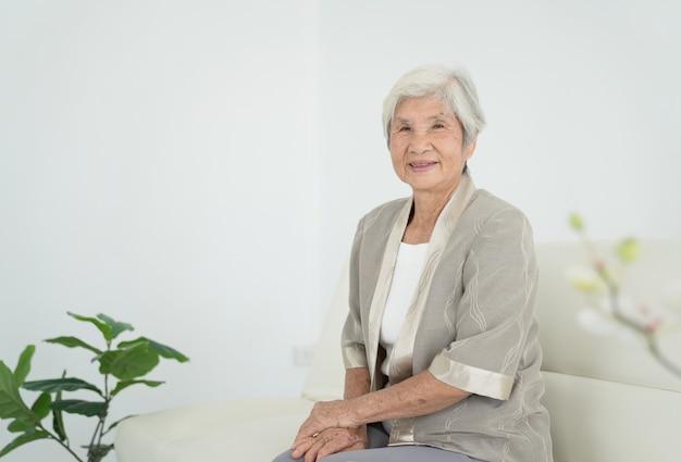 Lächelnde ältere frau, die auf sofa sitzt und kamera betrachtet. erwecke alte frau mit grauem haar und pyjama im frühen morgenlicht. porträt der älteren frau liegend und lächelnd.