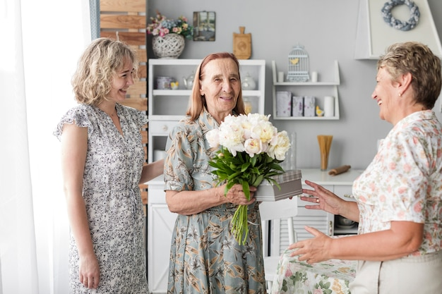Lächelnde ältere frau, die den blumenblumenstrauß und geschenk stehen mit ihrer tochter und großartigen tochter hält
