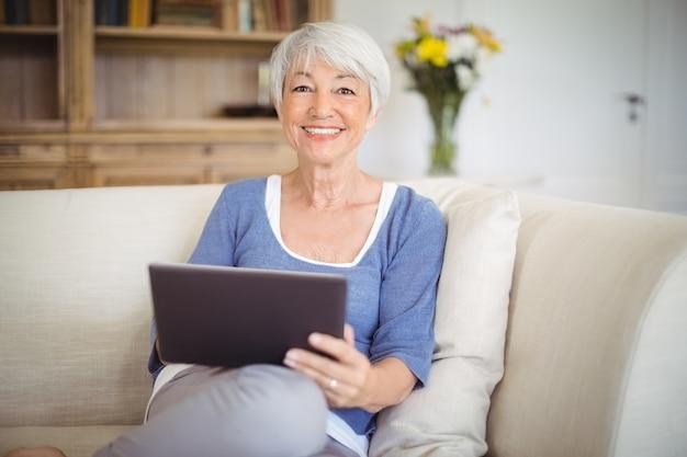 Lächelnde ältere frau, die digitales tablett im wohnzimmer verwendet