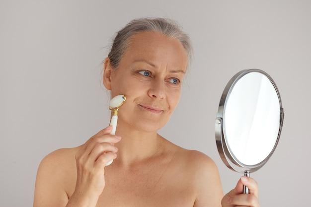 Lächelnde ältere frau, die ihr gesicht mit einer jaderolle massiert, während sie in den spiegel schaut