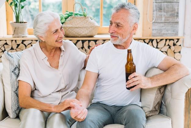 Lächelnde ältere frau, die ihren ehemann hält bierflasche betrachtet
