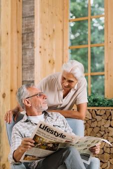 Lächelnde ältere frau, die ihren ehemann sitzt auf dem stuhl hält zeitung betrachtet