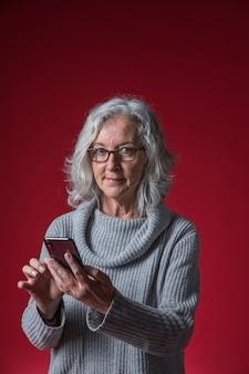 Lächelnde ältere frau, die in der hand das intelligente telefon schaut zur kamera gegen farbigen hintergrund hält