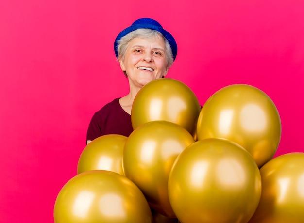 Lächelnde ältere frau, die parteihut trägt, steht mit heliumballons, die kamera auf rosa betrachten