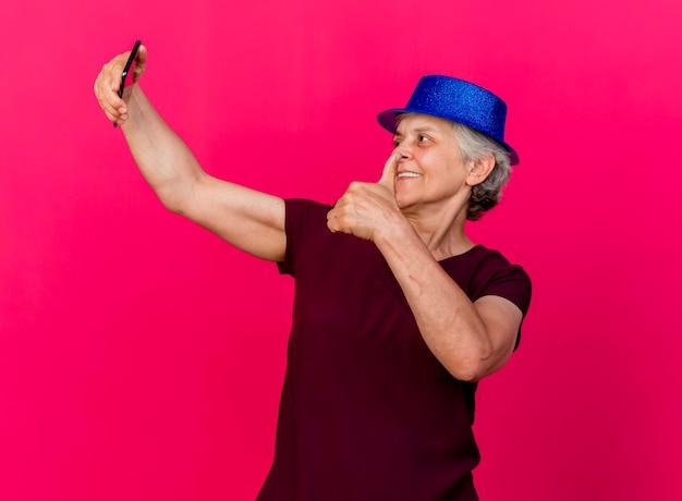 Lächelnde ältere frau, die partyhut daumen hoch hält hält und telefon auf rosa betrachtet