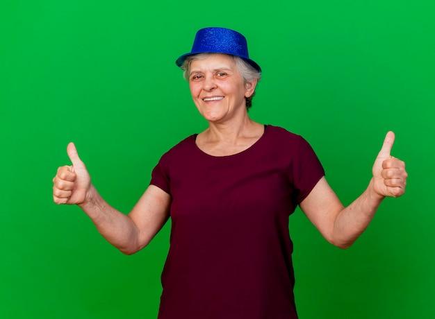 Lächelnde ältere frau, die partyhut daumen hoch mit zwei händen trägt kamera auf grün