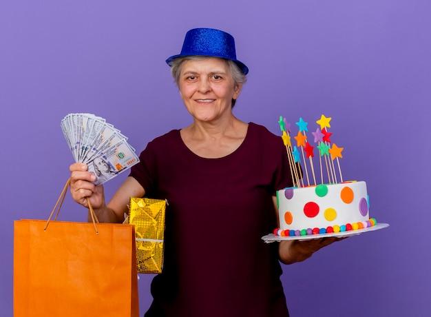 Lächelnde ältere frau, die partyhut trägt, hält geldgeschenkboxpapier-einkaufstasche
