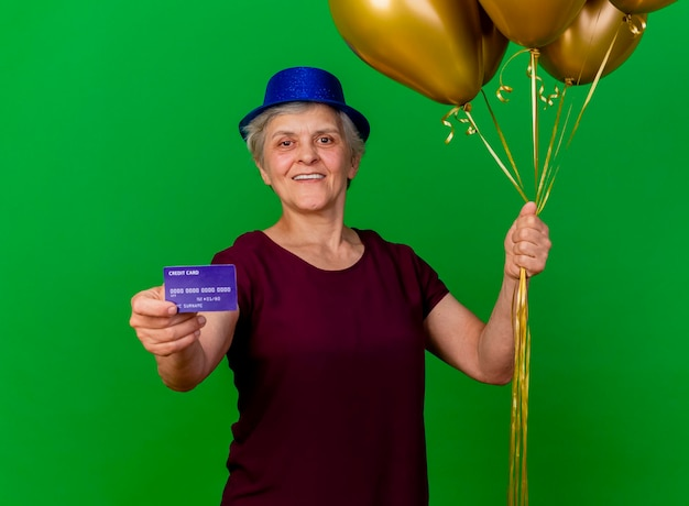 Lächelnde ältere frau, die partyhut trägt, hält kreditkarte und heliumballons auf grün
