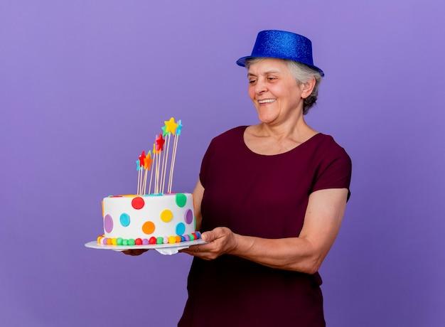 Lächelnde ältere frau, die partyhut trägt, hält und betrachtet geburtstagstorte lokalisiert auf lila wand mit kopienraum