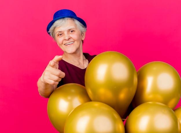 Lächelnde ältere frau, die partyhut trägt, steht hinter heliumballons, die auf kamera auf rosa zeigen