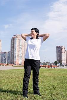Lächelnde ältere frau, die sich aufwärmt, bevor sie draußen im park trainiert