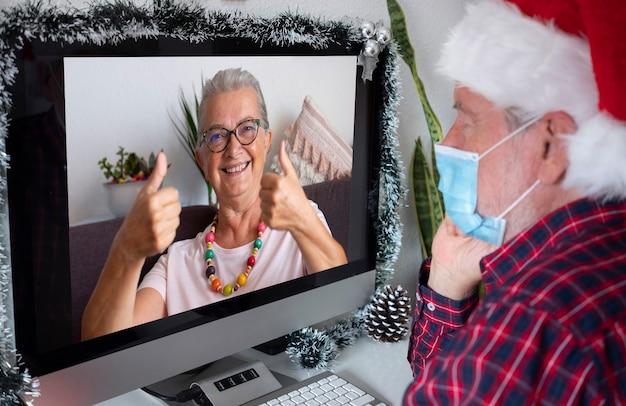 Lächelnde ältere frau, die über einen videoanruf für weihnachtsgrüße spricht und das erhaltene geschenk zeigt. mann mit weihnachtsmannmütze trägt wegen quarantäne wegen coronavirus-infektion eine chirurgische maske