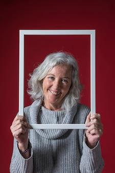 Lächelnde ältere frau, die weißen grenzrahmen vor ihrem gesicht gegen roten hintergrund hält