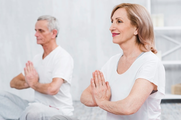 Lächelnde ältere frau, die yoga mit betendem handzeichen im haus tut