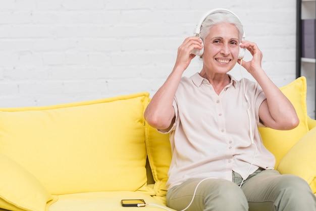 Lächelnde ältere frau, die zu hause auf hörender musik des gelben sofas auf kopfhörer sitzt
