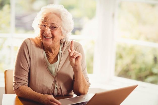 Lächelnde ältere frau, die zu hause finger unter verwendung des laptops anhebt