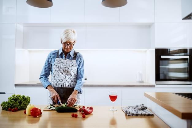 Lächelnde ältere frau in der schürze, die in der küche steht und gurke schneidet