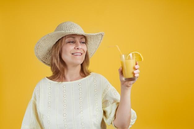 Lächelnde ältere frau in einem strohhut mit einem glas orangensaft-isolat auf hellgelbem hintergrund