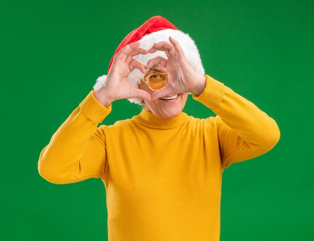 Lächelnde ältere frau in sonnenbrille mit weihnachtsmütze durch herzzeichen