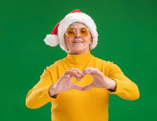 Lächelnde ältere frau in sonnenbrille mit weihnachtsmütze gestikuliert herzzeichen lokalisiert auf grünem hintergrund mit kopienraum