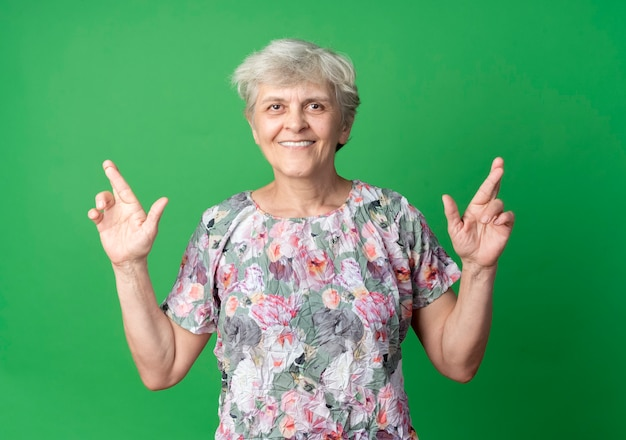 Lächelnde ältere frau kreuzt finger lokalisiert auf grüner wand