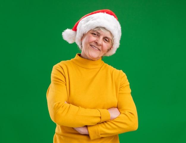 Lächelnde ältere frau mit weihnachtsmütze stehend mit verschränkten armen lokalisiert auf lila hintergrund mit kopienraum