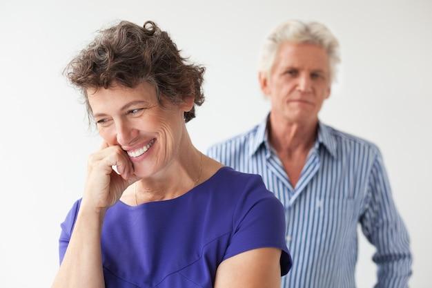 Lächelnde ältere frau und mann, die hinter